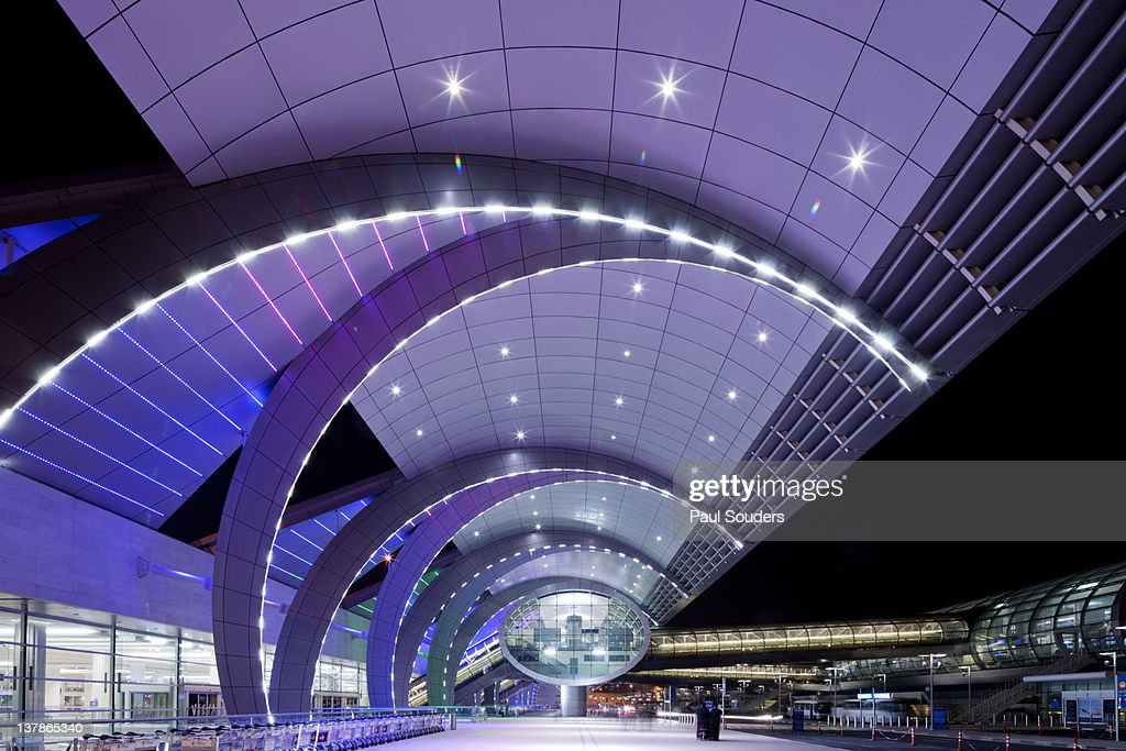 United Arab Emirates, Dubai, Colored lights adorn arched steel exterior of Dubai International Airport Terminal 3 at night