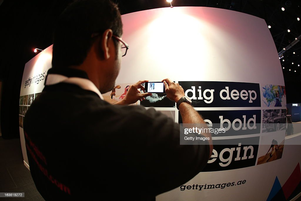 A Dubai Lynx attendee investigates the multimedia Getty Images wall, where a downloaded app on an iPad or Iphone called Ogle releases a movie content from a photograph, at Dubai Lynx 2013 at the Madinat Jumeirah on March 11, 2013 in Dubai, United Arab Emirates.