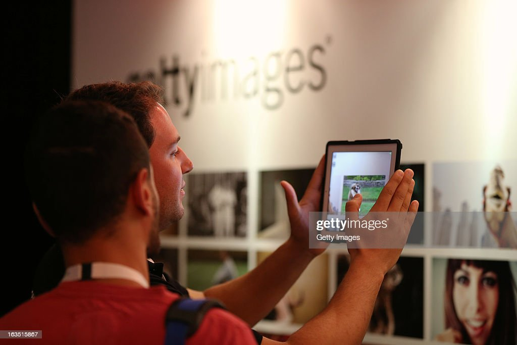 A Dubai Lynx attendees investigate the multimedia Getty Images wall, where a downloaded app on an iPad or Iphone called Ogle releases a movie content from a photograph, at Dubai Lynx 2013 at the Madinat Jumeirah on March 11, 2013 in Dubai, United Arab Emirates.