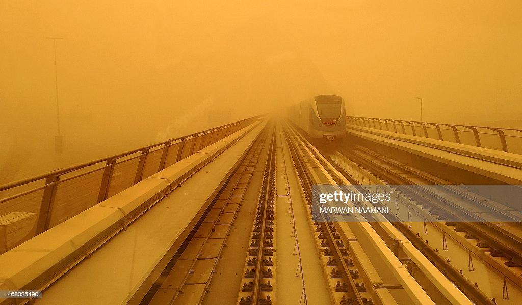 A Dubai metro train is seen driving amid a sandstorm that engulfed the city on April 02 2015 AFP PHOTO / MARWAN NAAMANI