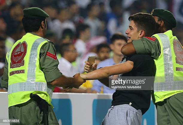 Dubai police arrest a pitch invader during the club world cup friendly football match between AC Milan and Real Madrid at the Sevens Stadium in Dubai...