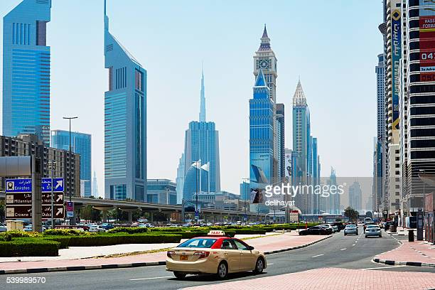 Dubai taxi in front of skyscrapers at Sheikh Zayed road