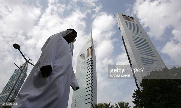A local man walks in front of Dubai's twin Emirates Towers on Sheikh Zayed road 08 January 2006 AFP PHOTO/KARIM SAHIB