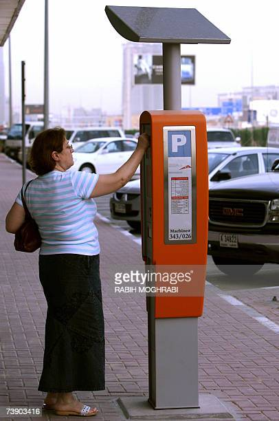 TO GO WITH AFP STORY IN FRENCH BY ALI KHALIL A Dubai resident uses his electronic card to pay to a car parking meeter powered by solar energy in...