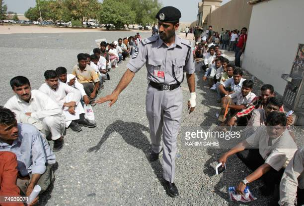 TO WITH AFP STORY BY HABIB TRABELSI A policeman organises lines of illegal workers mostly Asians queuing outside the Dubai immigration office 19 June...