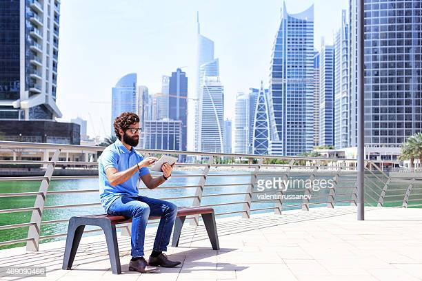 Dubai - Young men using digital tablet in the city