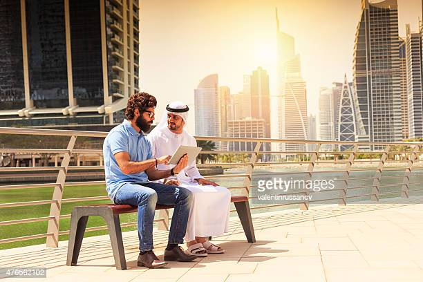 Dubai - Young mens using digital tablet in the city