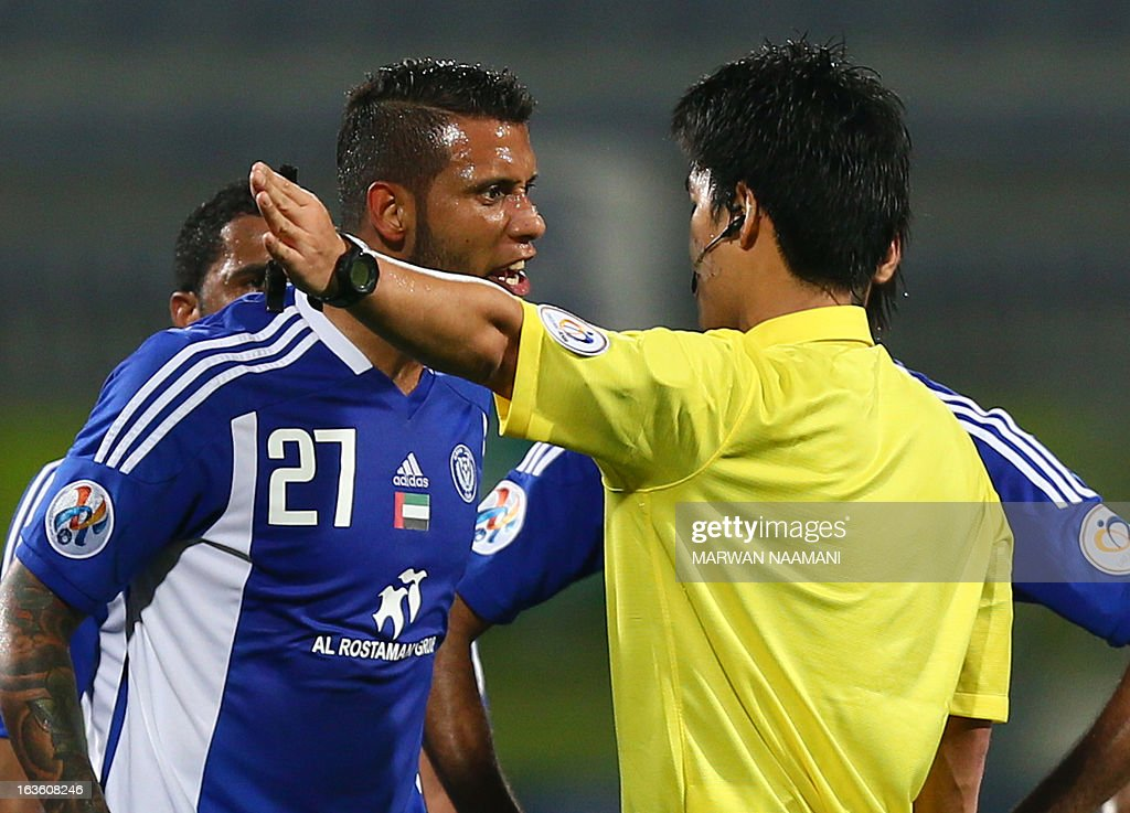 Dubai's al-Nasr player Leonadro Lima Da Silva (C) argues with Korean referee Kim Jong Hyeok (R) after he was given a red card for a dangerous tackle on Saudi Arabia's al-Ahli player Jario Palomino during their AFC Champions League soccer match in Dubai, on March 13, 2013. AFP PHOTO/MARWAN NAAMANI