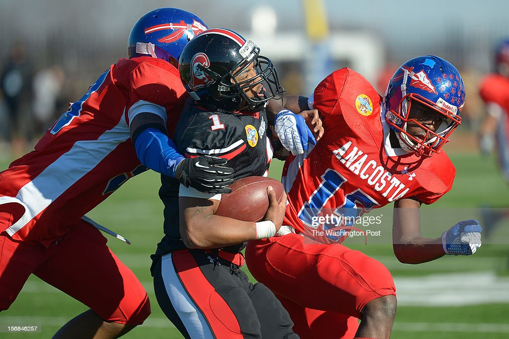 Dubar's QB Lamal Matthews , center, is hit from behind by Anacostia's Anton White, left, and Ahmahd Ryans as Dunbar defeats Anacostia 12 - 8 in the Turkey Bowl at Eastern High School in Washington DC, November 22, 2012 .