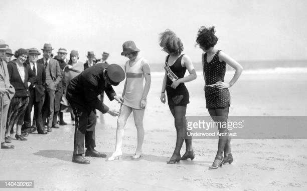 A dubious and curious police officer measures the hem of the newest in bathing fashions Atlantic City New Jersey circa 1921