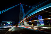 Harp bridge in Dubliny with cars passiing through by night