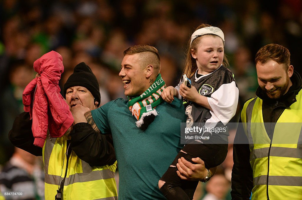 Dublin , Ireland - 27 May 2016; A Republic of Ireland supporter who went on the pitch at the end of the game with a child is escorted off the pitch after the game against the Netherlands during the 3 International Friendly between Republic of Ireland and Netherlands in the Aviva Stadium, Lansdowne Road, Dublin.