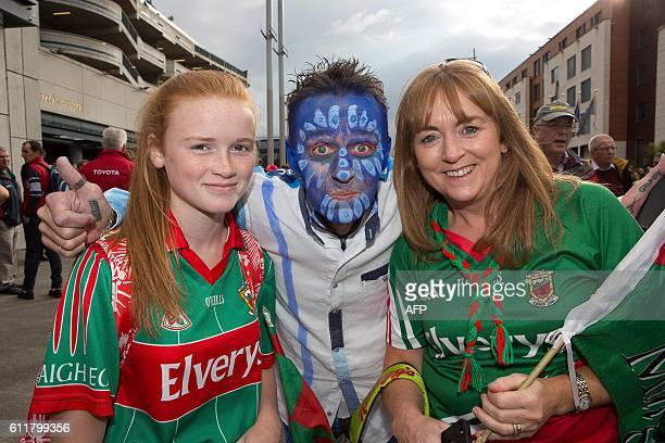 Dublin supporter Padraic O'Reilly flanked by Mayo supporters daughter and mother Sarah Barcoe and Anne Barcoe pose for a photograph outside Croke...