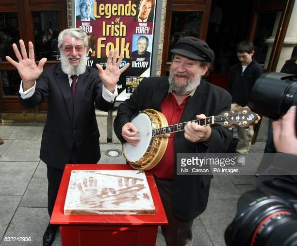 Dubliners frontman Ronnie Drew being entertained by fellow Dubliner Barney McKenna on the banjo after having his hands set in plaster at the Gaiety...