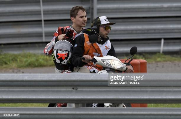 Ducati biker Jorge Lorenzo of Spain is transported to the pits after falling from his bike during the MotoGP race of the Argentina Grand Prix at...
