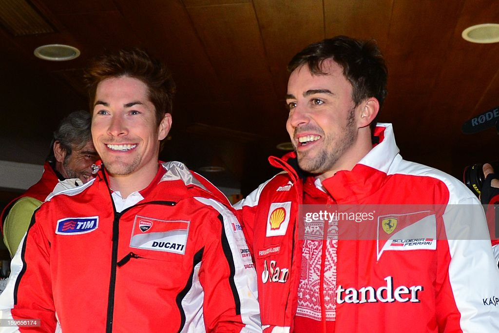Ducati Driver Nicky Hayden (L) and Ferrari driver Fernando Alonso pose during a show at the Wrooom, F1 and MotoGP press ski meeting, Ducati and Ferrari's annual media gathering on January 17, 2013 in Madonna di Campiglio. AFP PHOTO / GIUSEPPE CACACE