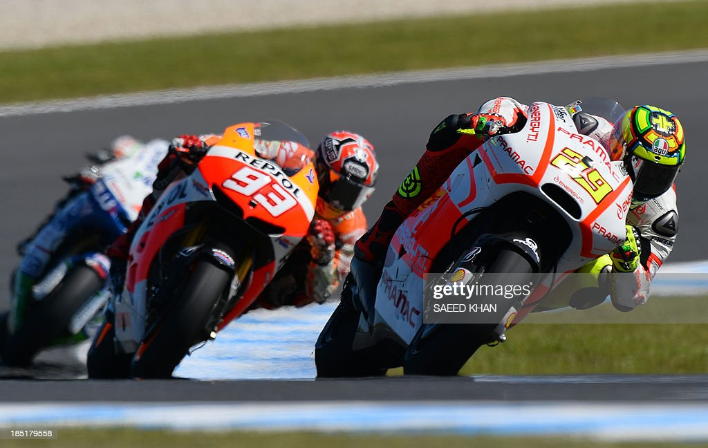 Ducati Pramac (R) rider Andrea Iannone of Italy powers his bike next to Repsol Honda Team Spanish rider Marc Marquez during the second practice session of the Australian MotoGP Grand Prix at Phillip Island on October 18, 2013. AFP PHOTO/ Saeed KHAN USE