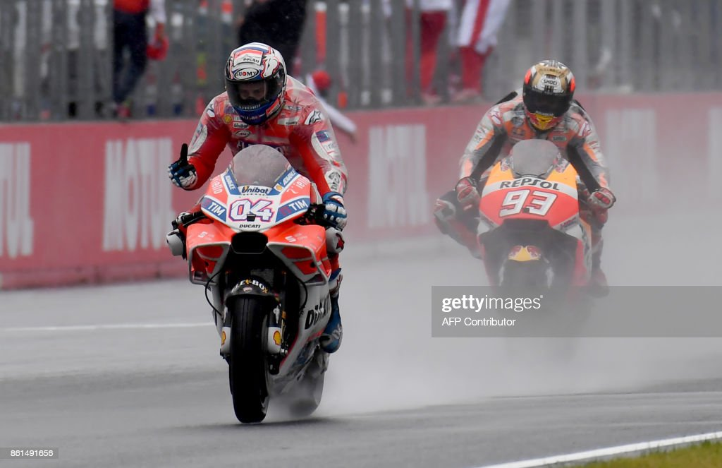 Ducati rider Andrea Dovizioso of Italy (L) flashes thumb-up while receiving a checkered flag ahead of Honda rider Marc Marquez of Spain (R) during the MotoGP Japanese Grand Prix at Twin Ring Motegi circuit in Motegi, Tochigi prefecture on October 15, 2017. /