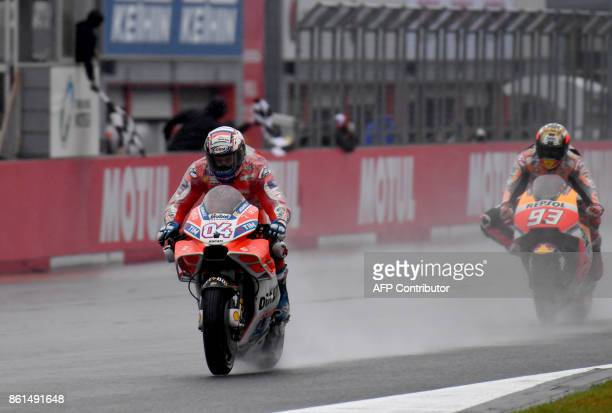 Ducati rider Andrea Dovizioso of Italy receives a checkered flag ahead of Honda rider Marc Marquez of Spain during the MotoGP Japanese Grand Prix at...