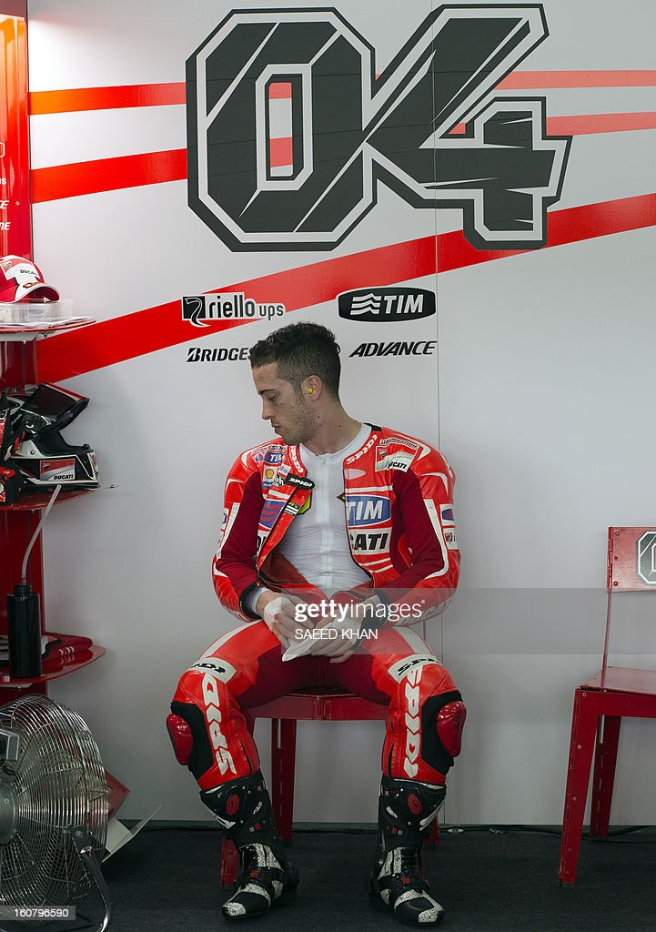 Ducati rider Andrea Dovizioso of Italy takes a rest inside the garage on the second day of the pre-season MotoGP test at the Sepang circuit in Sepang outside Kuala Lumpur on February 6, 2013. AFP PHOTO / Saeed Khan
