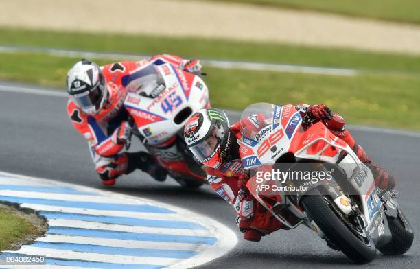 Ducati rider Jorge Lorenzo of Spain and Ducati Pramac rider Scott Redding of Britain negotiate a corner during the third practice session of the...