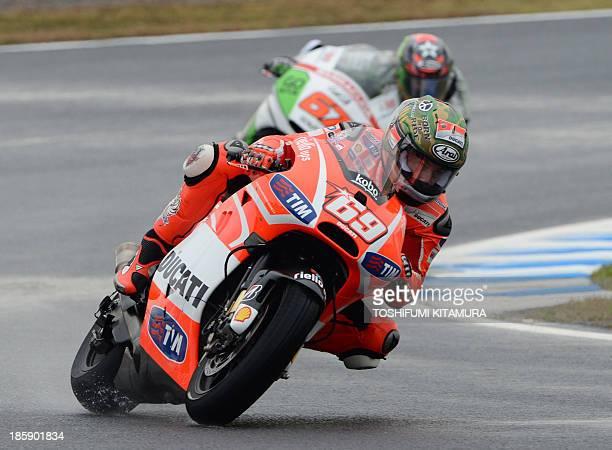 Ducati team rider Nicky Hayden of US takes a corner ahead of GoFun Honda Gresini rider Bryan Staring of Australia during the MotoGPclass qualifying...