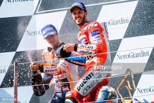 Ducati Team's Italian rider Andrea Dovizioso and Repsol Honda Team's Spanish rider Dani Pedrosa celebrate on podium after the the MotoGP Austrian...