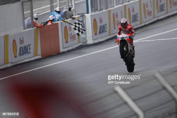 TOPSHOT Ducati Team's Italian rider Andrea Dovizioso celebrates winning the Malaysia MotoGP at the Sepang International circuit in Sepang on October...