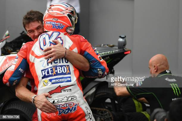 Ducati Team's Italian rider Andrea Dovizioso celebrates with a teammate after winning the Malaysia MotoGP at the Sepang International Circuit in...