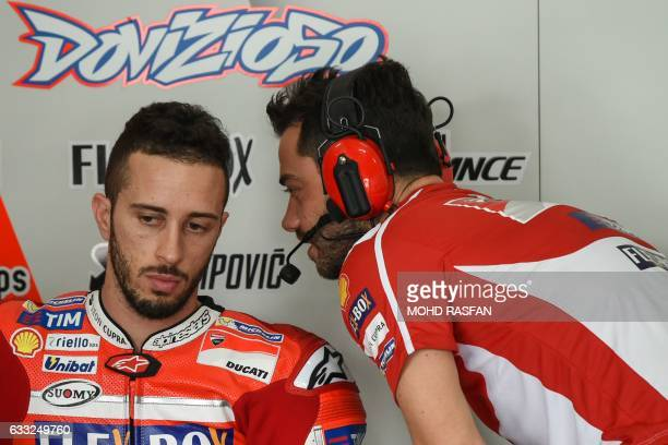 Ducati Team's Italian rider Andrea Dovizioso listens to a team member during the last day of the 2017 MotoGP preseason test at the Sepang...