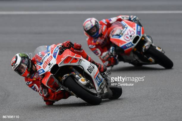 TOPSHOT Ducati Team's Spanish rider Jorge Lorenzo and Ducati Team's Italian rider Andrea Dovizioso compete during the Malaysia MotoGP at the Sepang...