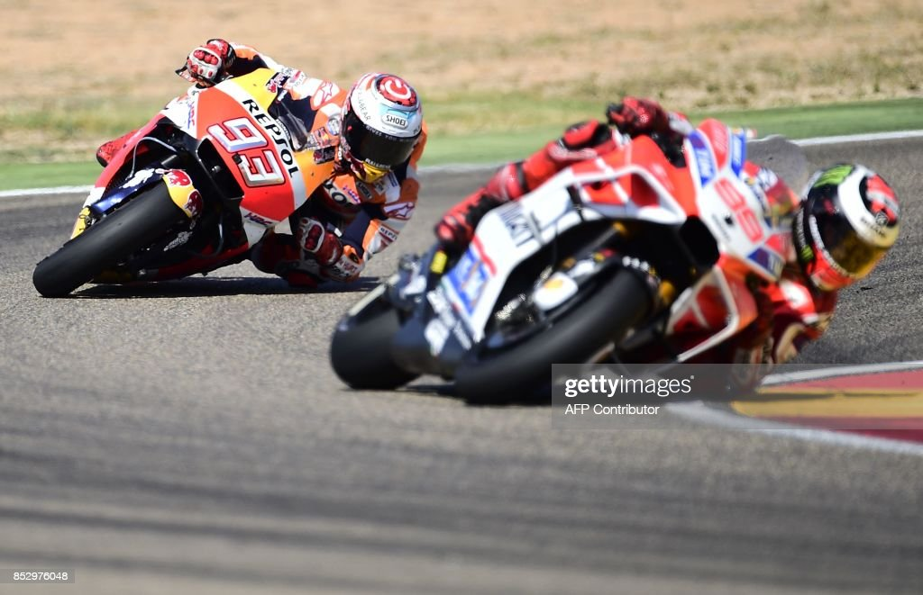 TOPSHOT - Ducati Team's Spanish rider Jorge Lorenzo (R) and Repsol Honda Team's Spanish rider Marc Marquez ride during MotoGP race of the Moto Grand Prix of Aragon at the Motorland circuit in Alcaniz on September 24, 2017. /