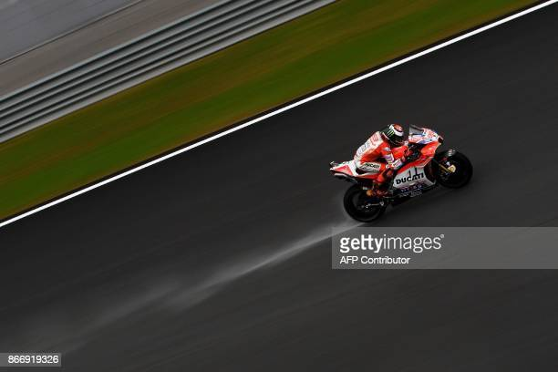 TOPSHOT Ducati Team's Spanish rider Jorge Lorenzo powers his bike on a wet track during the second practice session of the Malaysia MotoGP at the...