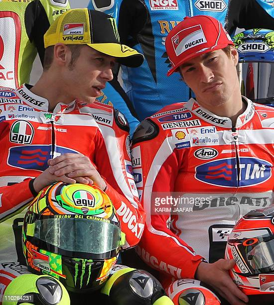 Ducati's MotoGP rider Valentino Rossi of Italy chats with his teammate Nicky Hayden of the US during the official photoshoot at the Losail...