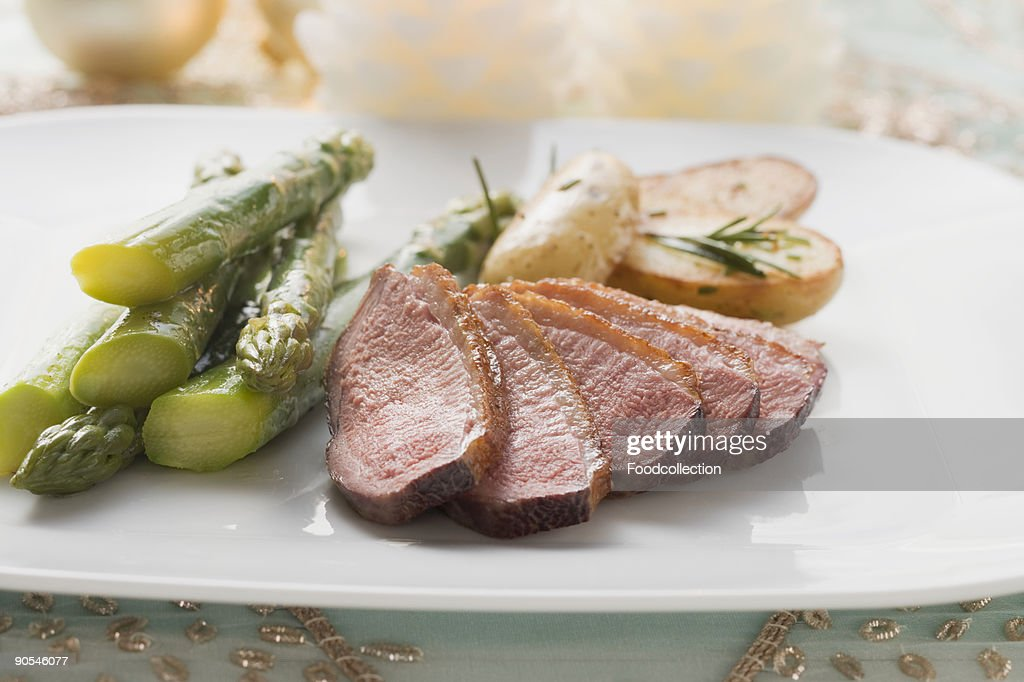 Duck breast with asparagus and potatoes, close up