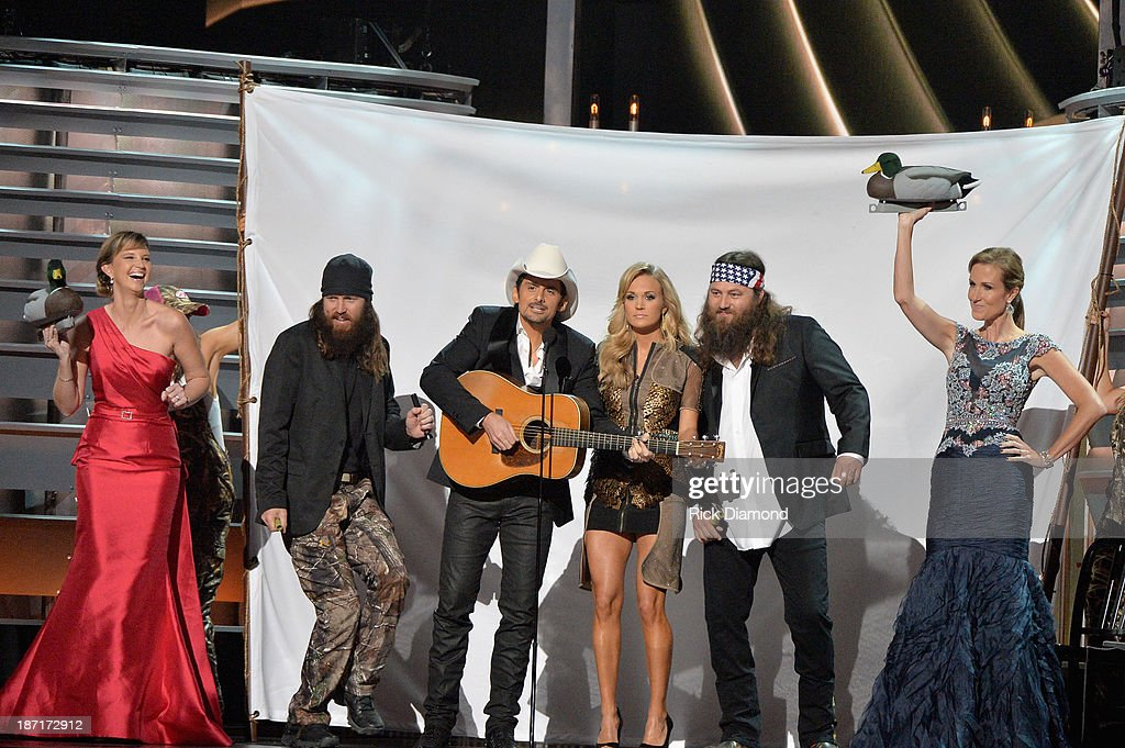 'Duck Dynasty' performs onstage with Hosts Brad Paisley and Carrie Underwood during the 47th annual CMA Awards at the Bridgestone Arena on November 6, 2013 in Nashville, Tennessee.