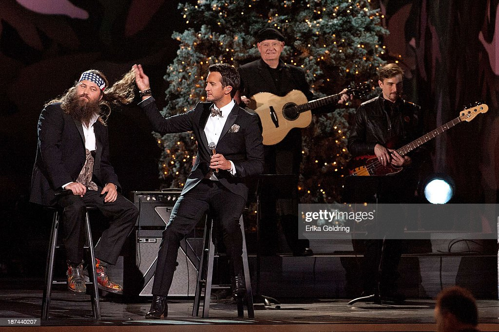 Duck Dynasty's Willie Robertson and Luky Bryan perform during the CMA 2013 Country Christmas on November 8, 2013 in Nashville, Tennessee.