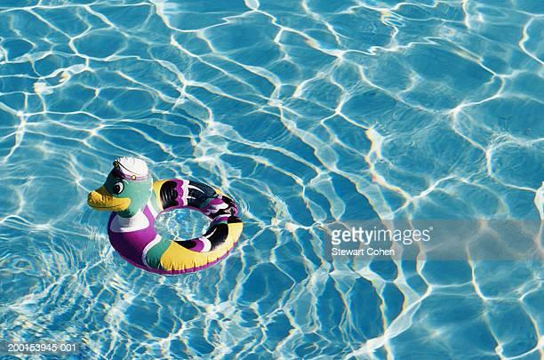 Duck shaped inner tube floating in pool