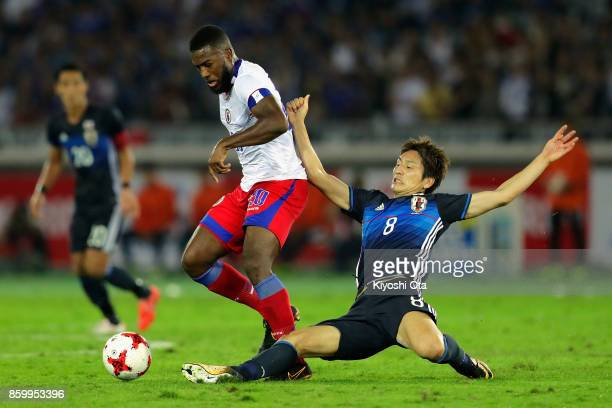 Duckens Nazon of Haiti is tackled by Genki Haraguchi of Japan during the international friendly match between Japan and Haiti at Nissan Stadium on...