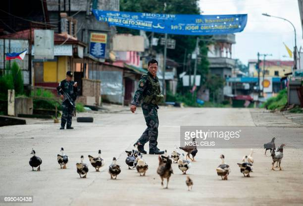 Ducks and chickens follow a police officer near a checkpoint in Marawi on the southern island of Mindanao on June 12 2017 Embattled Philippine troops...