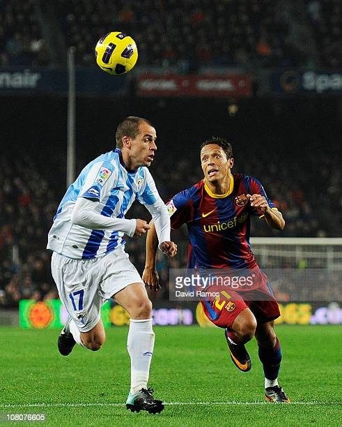 Duda of Malaga and Adriano of FC barcelona run for a high ball during the La Liga match between FC Barcelona and Malaga at Nou Camp on January 16...
