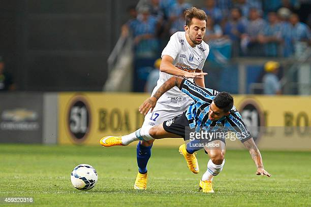 Dudu of Gremio battles for the ball against Everton Ribeiro of Cruzeiro during the match Gremio v Cruzeiro as part of Brasileirao Series A 2014 at...