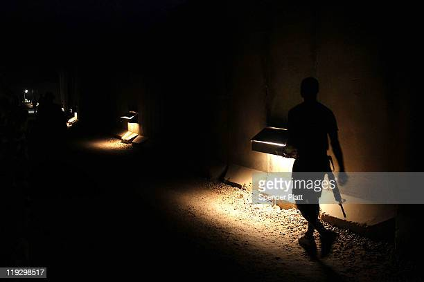 Due to security concerns over rocket attacks a soldier walks through a darkened base Kalsu on July 17 2011 in Iskandariya Babil Province Iraq As the...