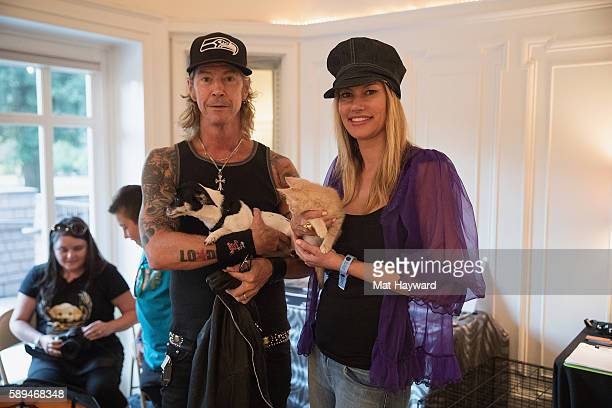 Duff McKagan of Guns and Roses and wife Susan HolmesMcKagan hold Motley Zoo rescue animals backstage during the Summer Camp music Festival at...