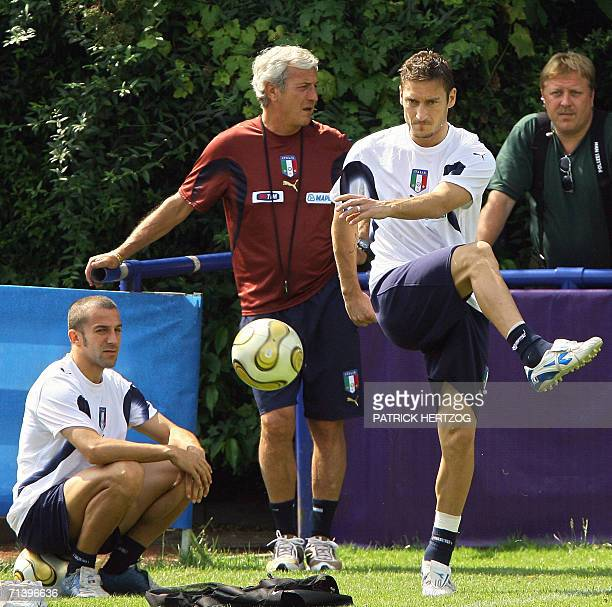 Italian forward Francesco Totti kicks the ball as teammate Alessandro Del Piero and coach Marcello Lippi look on during a training session 08 July...