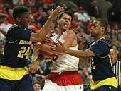 Duje Dukan of the Wisconsin Badgers tries to keep the ball away from Aubrey Dawkins and MuhammadAli AbdurRahkman of the Michigan Wolverines during...