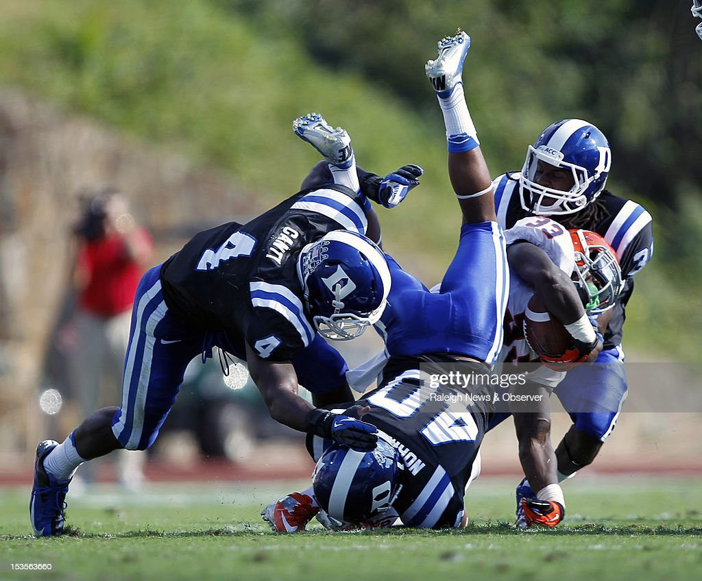 Duke defensive backs Walt Canty (4), Dwayne Norman (40) and Tony Foster (31) take down Virginia running back Perry Jones (33) during the second quarter at Wallace Wade Stadium in Durham, North Carolina, on Saturday, October 6, 2012.