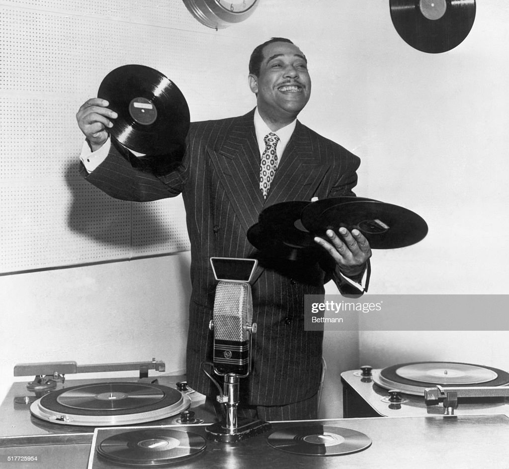Duke Ellington (1889-1974), bandleader, composer and arranger, has his hands full as he tries role of disc jockey. Photograph.