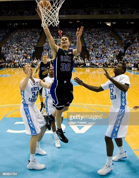 Duke guard Jon Scheyer shoots the ball between North Carolina forward David Wear and forward Ed Davis during a men's college basketball game at Dean...