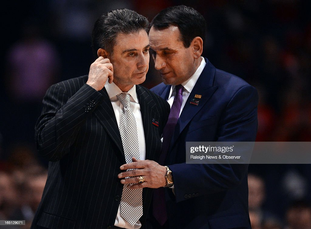 Duke head coach Mike Krzyzewski shares a moment with Louisville head coach Rick Pitino as medical technicians take care of injured Cardinals' guard...